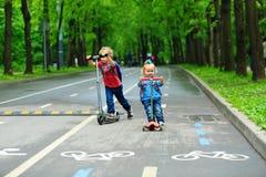 Petit scooters mignons d'équitation de fille de garçon et d'enfant en bas âge Photo libre de droits