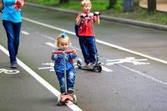 Petit scooters mignons d'équitation de fille de garçon et d'enfant en bas âge Photos stock