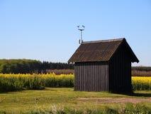 Petit Shack rural au champ jaune de viol Photographie stock