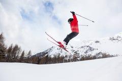 Petit skieur sautant dans la neige. image stock