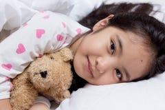 Petit sommeil asiatique adorable de fille avec la poupée d'ours images stock