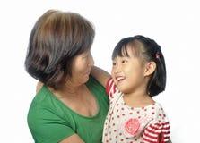 Petit sourire asiatique de petite-fille à sa grand-mère Photos libres de droits