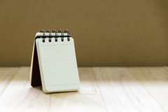 Petit support de bloc-notes de papier de carnet sur la table en bois pour écrire une information Photos stock