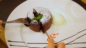 Petit tårta med glass Muffin med varm choklad i florsocker med glass Vit isolerat studioskott arkivfilmer