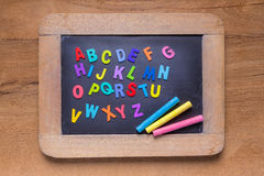 Petit tableau noir avec des craies de couleur et des alphabets anglais de couleur, Images libres de droits