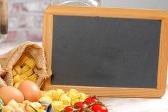 Petit tableau noir avec des pâtes, des oeufs et des tomates-cerises Photos libres de droits