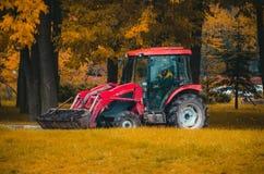 Petit tracteur dans le transport de parc d'automne les pots avec des fleurs pour la plantation Photos libres de droits