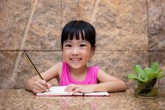 Petit travail chinois asiatique d'écriture de fille Photos stock