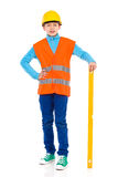 Petit travailleur de la construction posant avec un niveau d'esprit Photo libre de droits