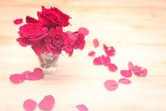 Petit vase avec les roses rouges et les pétales Photos stock