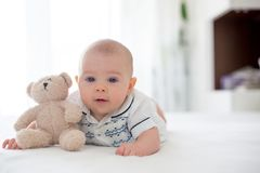 Petit vieux bébé garçon de quatre mois mignon, jouant à la maison dans le lit photos libres de droits
