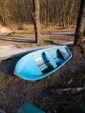 Petit vieux bateau de sauvetage en bois usé minable, peint paysage bleu et tôt de ressort avec les arbres nus sur la banque d'une images libres de droits