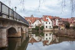 Petit village allemand vu à côté d'un pont avec sa réflexion i Photographie stock