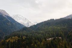 Petit village traditionnel en montagnes de l'Himalaya couvertes de forêt et de neige Photo libre de droits