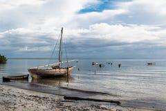 Petit voilier en bois sur l'eau à la plage photos stock