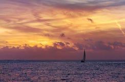 Petit voilier et coucher du soleil avec de l'eau les nuages rouges et bleu Image libre de droits