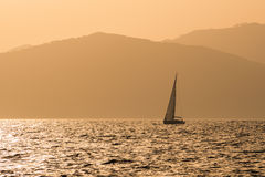 Petit yacht au coucher du soleil Photographie stock libre de droits