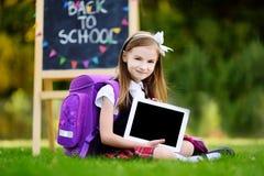 Petite écolière adorable tenant le comprimé numérique Photo stock