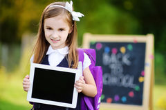 Petite écolière adorable tenant le comprimé numérique Image stock