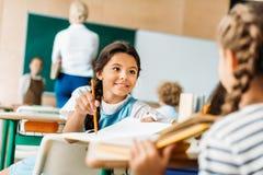 petite écolière heureuse parlant au camarade de classe photos stock