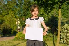 Petite écolière mignonne avec la page du papier blanche pour faire de la publicité sur le fond de nature Images stock