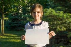 Petite écolière mignonne avec la page du papier blanche pour faire de la publicité sur le fond de nature Photo libre de droits