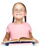 Petite écolière mignonne avec un livre photo libre de droits