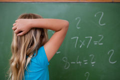 Petite écolière pensant tout en rayant le dos de sa tête photographie stock libre de droits