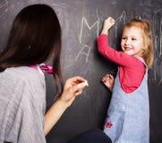 Petite écriture blonde mignonne de fille sur le tableau noir dans la salle de classe avec le professeur, concept de personnes d'é Image stock