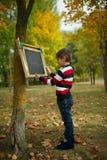 Petite écriture heureuse de garçon sur le tableau noir Photo libre de droits