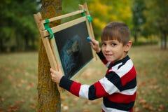 Petite écriture heureuse de garçon sur le tableau noir Photo stock