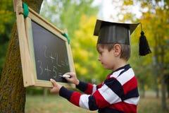 Petite écriture heureuse de garçon sur le tableau noir Images stock