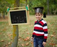 Petite écriture heureuse de garçon sur le tableau noir Photographie stock