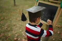 Petite écriture heureuse de garçon sur le tableau noir Photographie stock libre de droits