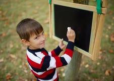 Petite écriture heureuse de garçon sur le tableau noir Photos libres de droits