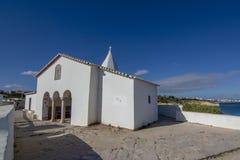 Petite église blanche sur la falaise à la plage d'Armacao de Pera, Alg Image libre de droits
