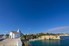 Petite église blanche sur la falaise à la plage d'Armacao de Pera, Alg Photographie stock