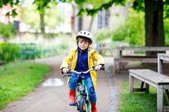 Petite équitation préscolaire mignonne de garçon d'enfant sur la bicyclette en parc Image stock