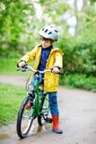 Petite équitation préscolaire mignonne de garçon d'enfant sur la bicyclette en parc Photographie stock