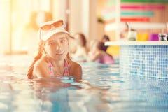 Petite adolescente dans la piscine de station de vacances d'hôtel près d'une barre Images libres de droits
