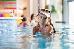 Petite adolescente dans la piscine de station de vacances d'hôtel près d'une barre Photos stock