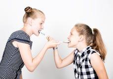 Petite amie deux mignonne mangeant les lucettes lumineuses Gosses drôles Les meilleurs amis choient et pose Images stock