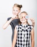 Petite amie deux mignonne mangeant les lucettes lumineuses Gosses drôles Les meilleurs amis choient et pose Photographie stock libre de droits