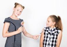 Petite amie deux mignonne mangeant les lucettes lumineuses Gosses drôles Les meilleurs amis choient et pose Image stock
