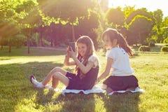Petite amie gais jouent avec le smartphone se reposant sur un pré en parc Photo libre de droits