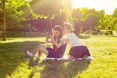 Petite amie gais jouent avec le smartphone se reposant sur un pré en parc Le concept des personnes, enfants, technologie, f Images stock