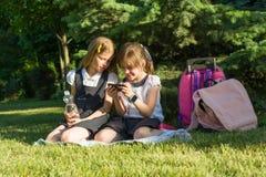 Petite amie gais jouent avec le smartphone se reposant sur un pré en parc Le concept des personnes, enfants, technologie, franc Image libre de droits