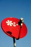 Petite antenne parabolique rouge avec le ciel bleu Images libres de droits