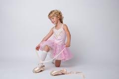 Petite ballerine étonnante attachant des pointes dans le studio Photos libres de droits