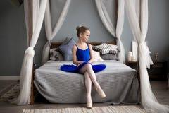 Petite ballerine s'asseyant sur un lit Rêves mignons de petite fille de devenir une ballerine Photo libre de droits